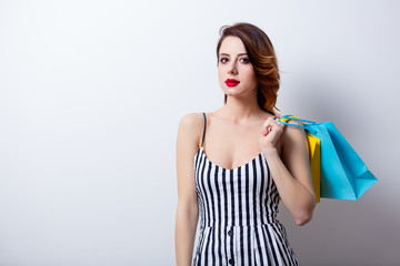portrait of beautiful young woman with colorful shopping bags on the wonderful studio background