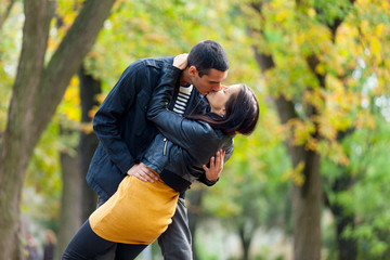 photo of cute couple kissing on the wonderful autumn park background