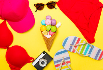 photo of swumsuit, sunglasses, hat, sandals, marshmallows in waffle cone and camera on the wonderful yellow studio background