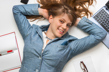 Smiling woman lying on back with laptop and smartphone