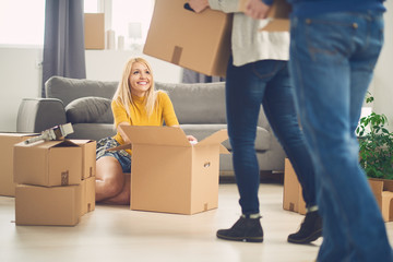 Friends helping young girl to move in new apartment, boxes everywhere