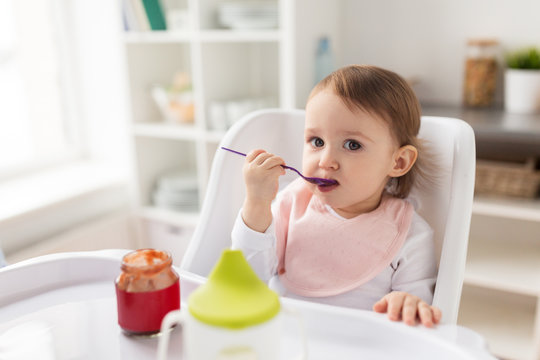baby girl with spoon eating puree from jar at home