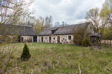 The yard of an abandoned village farm. Stone barns and a well. Spring in the Region Podlasie, Poland.