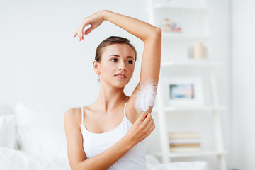 woman with feather touching her armpit at home