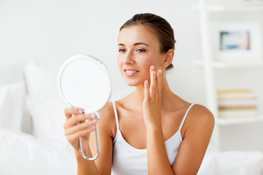 beautiful woman with mirror touching her face skin