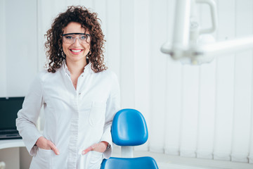 Portrait of female dentist. She standing at her office and she has beautiful smile.