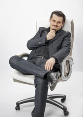 A young businessman is sitting on a chair in his office and he is touching his chin.