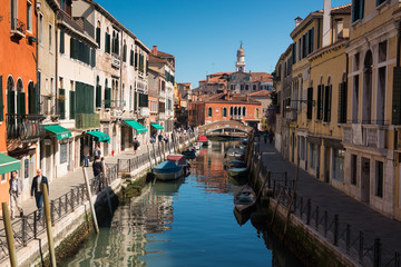 Narrow street with a canal, bridge, boats and tourists in Venice
