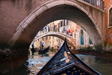 View from gondola under old bridge in street of Venice