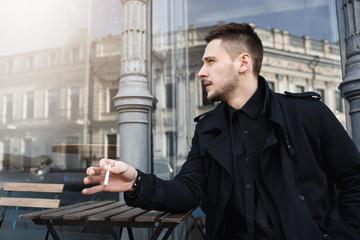 Handsome man in total black having cigarette, looking away.