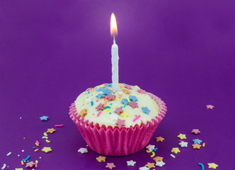 Bright purple background with single white cup cake in pink paper case and lit candle with colour star sprinkles for birthday celebration