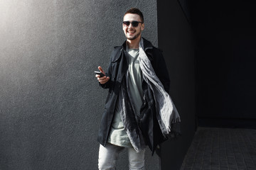 Young handsome guy in cool spring outfit standing in street.