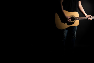 The guitarist in jeans plays an acoustic guitar, on the right side of the frame, on a black background. Horizontal frame
