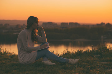 Sad woman thinking while writing at her notebook with a sunset over the city.