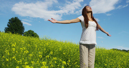 in a beautiful sunny day a woman is happy in nature . concept of happiness and nature. a meadow of yellow flowers and the blue sky . colorful nature