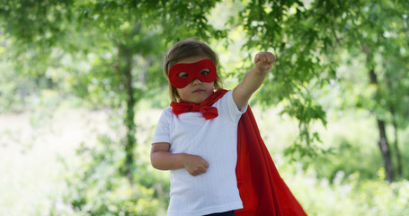 in a beautiful and happy sunny day , a little girl dressed as a super hero makes expressions and try to fly in the colorful nature , the child laughs happy . concept of happiness , love and nature.