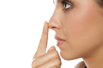 Profile of young woman touching her nose