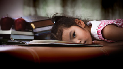 Child asian little girl is lying down on book and bored to read a book in dark tone