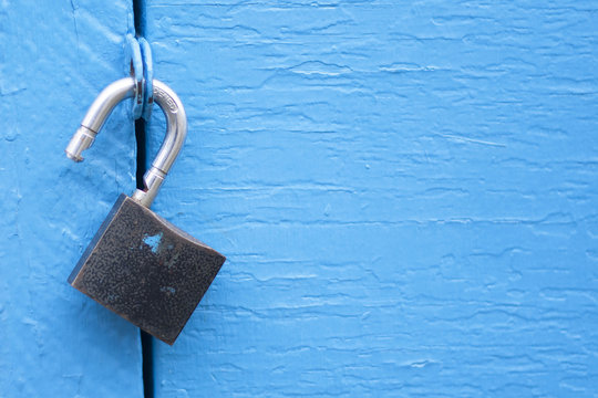 Open lock on blue door background - template for text security business web concept. Unlock padlock - secure, protection, insurance and safety access, computer, IT, internet technology.