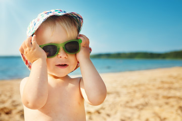 little boy smiling at the beach in hat with sunglasses