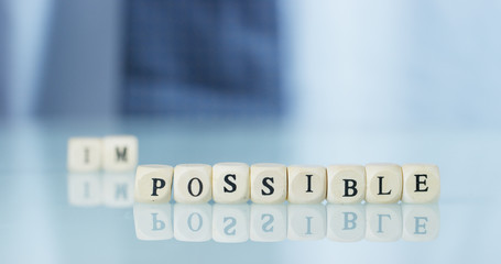 """A hand turns the word """"Impossible"""" to """"Possible"""" throwing away the letters. Concept: commitment, believe it until the end, everything is possible."""