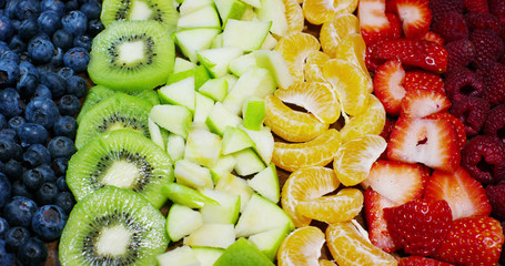 of fresh fruit mix composition, with strawberry, apple,blueberry,raspberry,kiwi, orange. Salad of fresh and exotic tropical fruit to eat in the summer.Explosion of colors, freshness,vitamins and taste