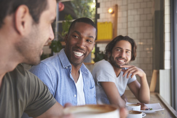 Three Male Friends Meeting In Coffee Shop