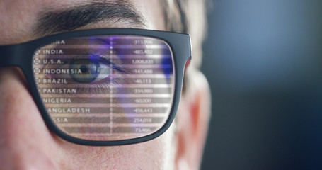 Close up of young businessman with blue eyes wearing the glasses looking on the waveform lines and data