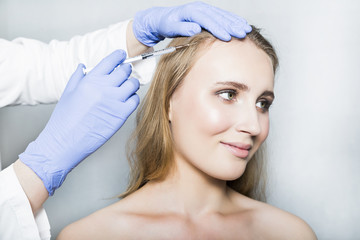 Doctor aesthetician makes head beauty injections to female patient on white background