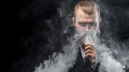 Vaping man holding a mod. A cloud of vapor. Black background. Studio shooting.