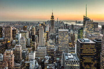 Fototapete - New York City. Manhattan downtown skyline with illuminated Empire State Building and skyscrapers at dusk.