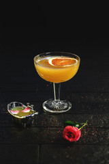 Bright yellow alcohol cocktail garnished with orange and rose on black background