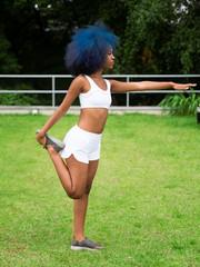 Mulher negra se equilibrando para alongamento ao ar livre