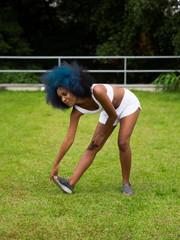 Mulher negra alongando as pernas ao ar livre