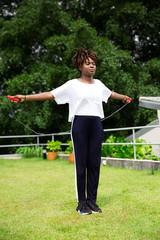 Mulher negra jovem pulando corda ao ar livre