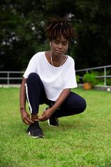 Mulher negra ouvindo música e amarrando o tênis