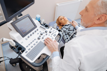 Qualified doctor providing ultrasound scanning in the hospital