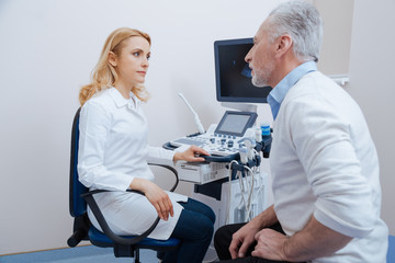 Attractive sonographer having conversation with aged patient at work