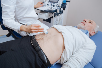 Qualified practitioner providing ultrasonic abdomen monitoring at work