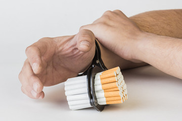 Cigarettes and hand of a man in handcuffs. The concept of nicotine addiction. Isolated on a white background.