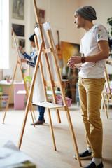 Learner of art-school standing by easel