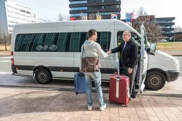 Taxi Driver Shaking Hands With Man By Van At Airport