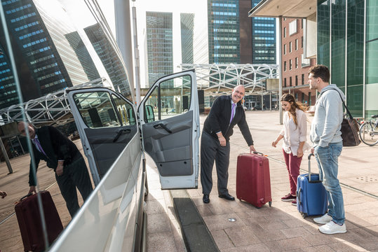 Driver And Passengers With Luggage By Van At Airport