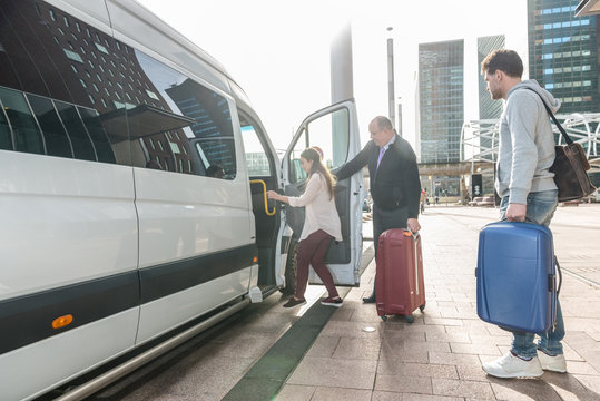 Driver Assisting Female Passenger To Board Van At Airport