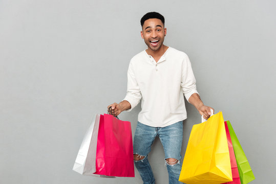 Happy african man holding shopping bags.