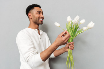 Cheerful man standing over grey wall with flowers and ring.