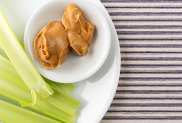 Celery stalks with peanut butter on a white plate atop a blue striped tablecloth.