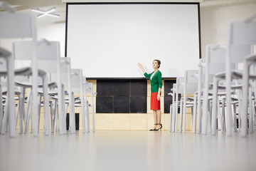 Young teacher pointing at whiteboard while explaining new topic