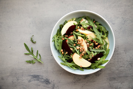 Arugula, beets, apples and nuts salad in bowl on gray background