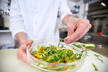 Chef adding pinch of salt into vegetarian salad